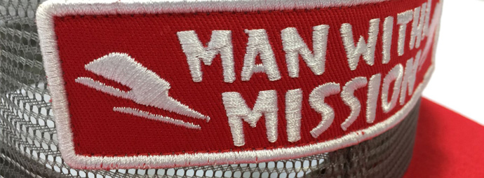 Sewn on fabric badge with flat emb detail